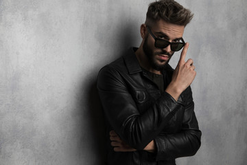 portrait of casual man in leather jacket touching his sunglasses