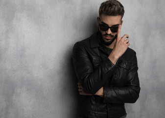 young man in leather jacket fixes his sunglasses