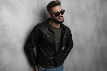 portrait of curious man wearing leather jacket and sunglasses