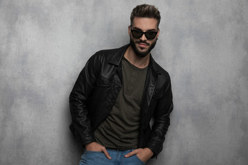 portrait of relaxed man wearing leather jacket and sunglasses smiling