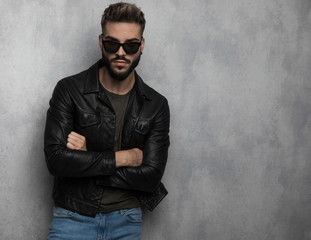 portrait of confident unshaved man wearing leather jacket and sunglasses
