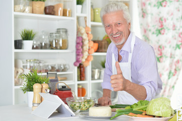 Portrait of senior man showing thumb up while preparing dinner in kitchen