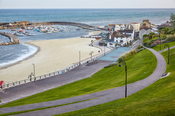 The beautiful view from the Seafront gardens to the Cobb harbor of Lyme Regis. West Dorset. England