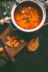 Cooking pot with tasty lentil soup and ladle on dark rustic kitchen table background with ingredients, top view with copy space. Healthy vegan food concept