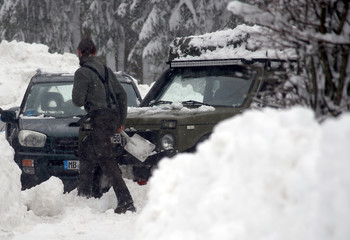 A man uses a shovel to free his car after heavy snowfall near Reitham