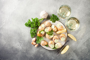 Escargots de Bourgogne - Snails with herbs butter on gray background. Top view