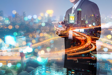 Double Exposure, Businessman use Mobile Smartphone device with Night City Building