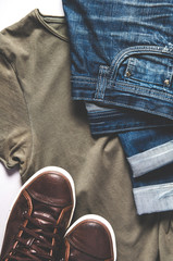 Men's clothing - jeans, sneakers and t-shirt. Flat lay and top view