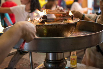 hand cense joss stick to at an incense burne