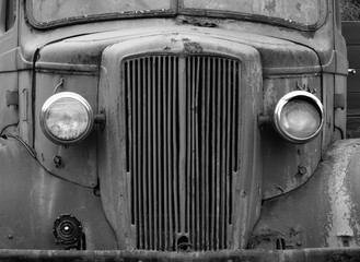 monochrome front view of an old abandoned rusty 1940s truck