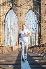 Young athlete jogging on Brooklyn Bridge in New York City