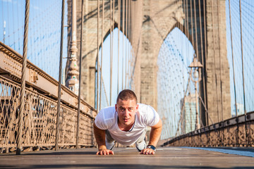Young athlete doing pushups on Brooklyn Bridge in New York City