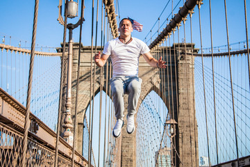 Young athlete exercising and jumping on Brooklyn Bridge in New York City