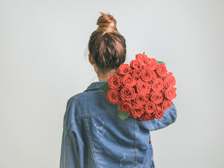 Back view of young woman in denim jacket holding bunch of Living Coral roses on shoulder. Girl with bun updo in jeans holding flowers in Color of Year 2019 Living Coral. Copy space.
