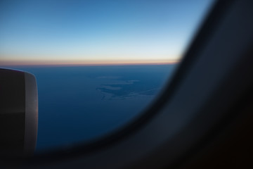 View from the window to airplane engine on runway of airport. Above the sky, on sunrise.