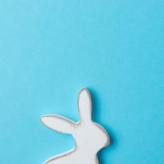Easter bunny decoration on blue background. Minimal Easter concept.