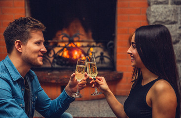 Cheerful young man and woman sit in front of each other and smile. They hold glasses with champaigne and touch them. Couple smile. They sit at fireplace.