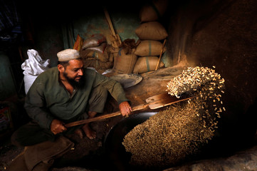 Man cooks peanuts for sale at a shop in Peshawar