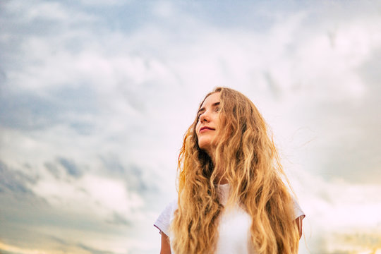 A white woman against a background of sky and clouds. Women force rights self-confident concept. feminism and beauty. the struggle for gender equality .