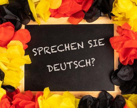blackboard with german colors and german text sprechen sie deutsch, in english do you speak german?
