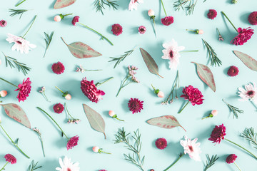 Flowers composition. Eucalyptus leaves and pink flowers on pastel blue background. Flat lay, top view