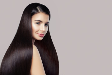 Haircare concept. Beauty brunette woman with long straight healthy hair on pink