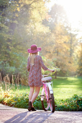 Back view of slim blond fashionable long-haired attractive girl in short dress and pink hat at lady bicycle outdoors on paved summer park alley on beautiful foggy green and golden trees background.