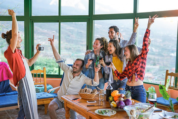 Group of friends taking photo with old vintage camera at dinner eating fresh vegetables and drinking red wine - Happy people dining and having fun together in villa farm house - Friendship concept