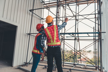 Construction engineer teamwork are inspection site constructing and installation steel scaffolding platform., Project manager and architect are looking and pointing to problem of structure steel.