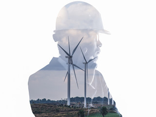 The double exposure image of the engineer standing back during sunrise overlay with wind turbine image. The concept of engineering, power, electricity, environment and future.