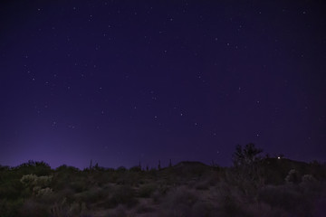 The desert at night shows starry skies and wilderness landscape east of Phoenix, Arizona. Light pollution is making shooting these night scapes more difficult to find dark skies without city glare