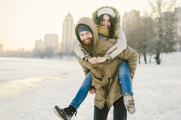 Theme New Year Christmas Mood Winter Snow Holidays Valentine Day. Young Caucasian couple lovers joy, laughter fooling water in city park. man holds woman on shoulders as backpack