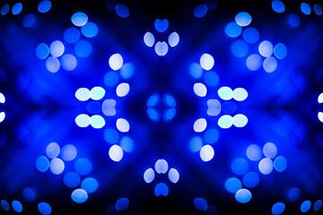Abstract symmetric glitter defocused blue lights bokeh texture on black background