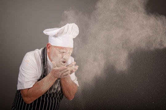 Mature chef sneezing in a pile of flour