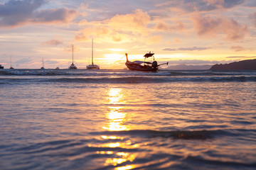 Traditional thai boat at sunset beach.