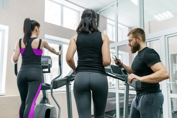 Young athletic women on treadmill, personal instructor coaching and helping client woman. Fitness, sport, training, people concept.