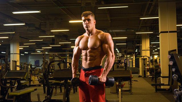 Man bodybuilder posing standing in big gym