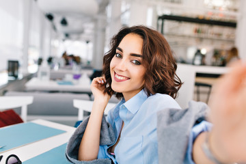 Selfie-portrait  of cute brunette girl with short hair sitting at table in gray plaid on terrace in restaurant. She wears blue shirt and looks happy.