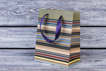 Paper gift bag on wooden background. Striped shopping bag. Business, retail, sale and commerce concept.