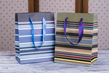 Two paper shopping bags with satin handles. Close up striped gift bags on wooden table. Gift packets design.