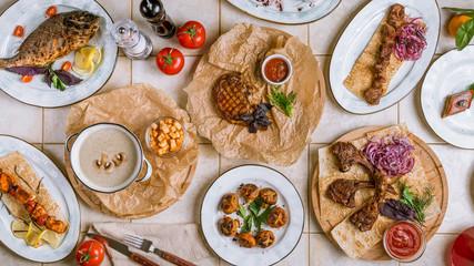 Assorted dishes top view pork ribs, beef steak, rack of lamb, dorado, cream soup, salmon kebab