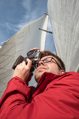 A handsome man - a photographer in a red jacket takes pictures on a yacht, against the background of white sails and blue sky, on a sunny summer day.