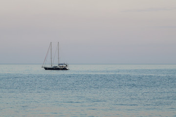 A small yacht with a sail in the sea at dusk in the evening.
