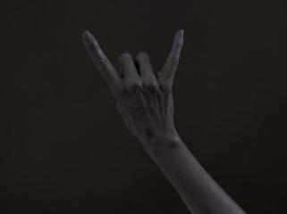 Goat gesture on a dark background. Black hand doing rock symbol. Hands up