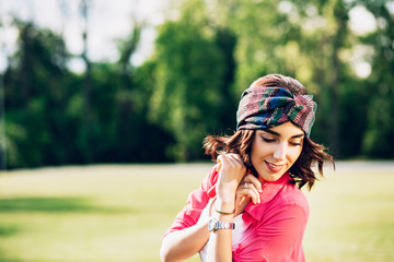 Closeup portrait  of pretty brunette girl in bandana walking in summer park. She wears white clothes, long pink shirt. She is smiling down.