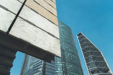 From below view of contemporary architectural buildings exterior with glass and concrete in design