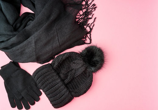 Flat lay winter or autumn warm woman accessories - black knitted scarf, hat on bright pink background, copy space
