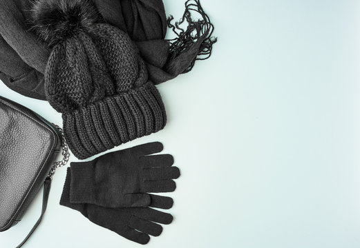 Flat lay winter or autumn warm woman accessories - black knitted scarf, hat, bag on bright blue background, copy space