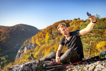 Traveler man after trekking sitting on rock looking at mountain view and making selfie photo