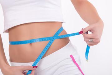 Woman measuring her waist with a tape measure.